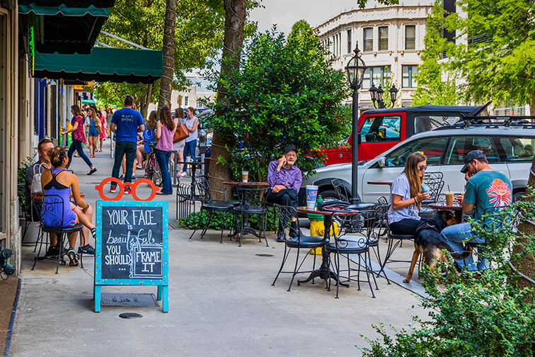 Dining and socializing on a sunny Sunday on Battery Park Ave Asheville North Carolina; Courtesy of MilesbeforeIsleep/Shutterstock