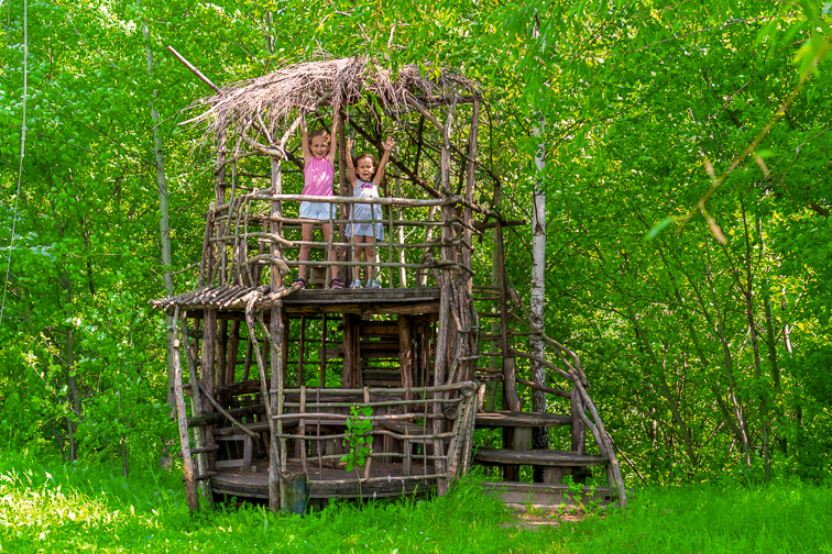 Two little happy girls in a wooden tree house on a sunny day. Sisters rejoice in the summer. The concept of summer.; Courtesy of UfaBizPhoto/Shutterstock