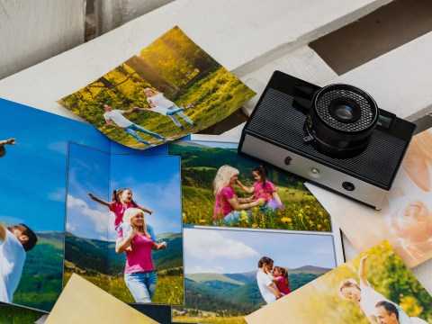 Photo album with photos of travel and vintage old camera on a background ; Courtesy of Andrew Angelov/Shutterstock