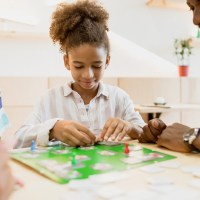 frican-american family playing board game in cafe; Courtesy of Lifield Studios/Shutterstock