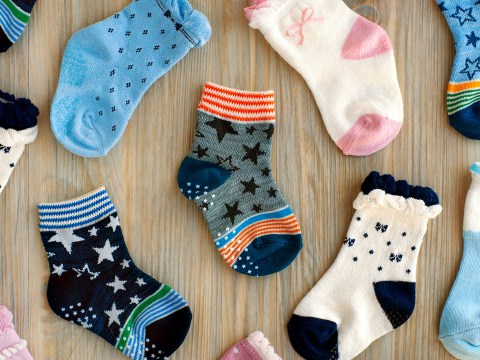 baby socks flat lay on a table top; Courtesy of Evgeniya369/Shutterstock