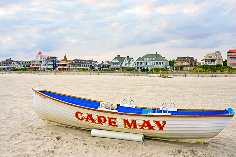 View of a boat with a Cape May sign on the beach in Cape May, New Jersey, USA.; Courtesy of EQRoy/Shutterstock