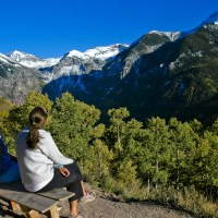 family mom and daughter sit on top of mountain and look at view; Courtesy Colorado Tourism Office