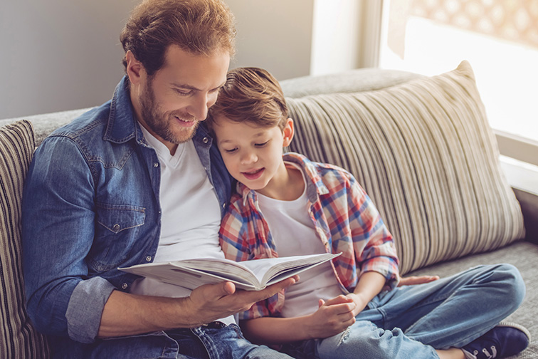 Father and son are reading a book and smiling while spending time together at home; Courtesy of George Rudy/Shutterstock