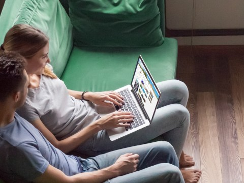 parents research travel on their laptop sitting on sofa; Courtesy of fizkes/Shutterstock