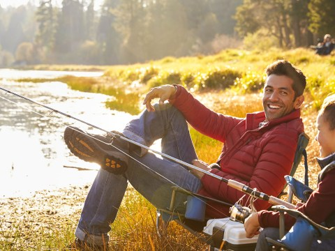dad sitting with son camping by lake wearing jacket; Courtesy Monkey Business Images/Shutterstock