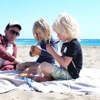 Family on a beach blanket in the sand.; Courtesy of Twenty20