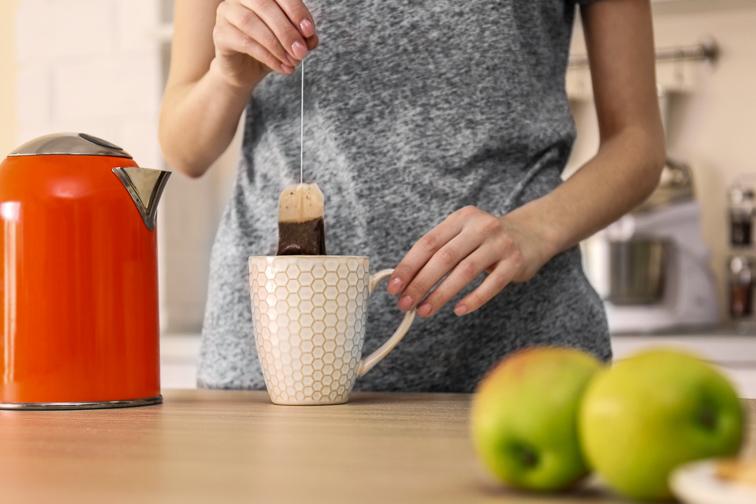 woman making herbal tea in kitchen; Courtesy Africa Studio/Shutterstock