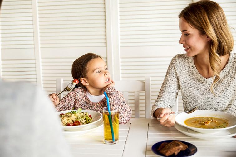 little girl talking at dinner; Courtesy Syda Productions/Shutterstock