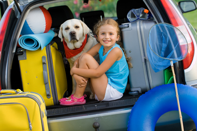 A little girl and her yellow labrador ready to embark on their next camping trip.