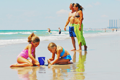 A family playing on the beach at the Holiday Shores Motel in Myrtle Beach.