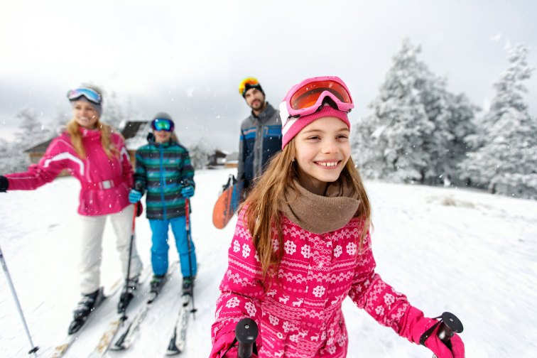 A family skiing.; Courtesy of Lucky Business/Shutterstock.com