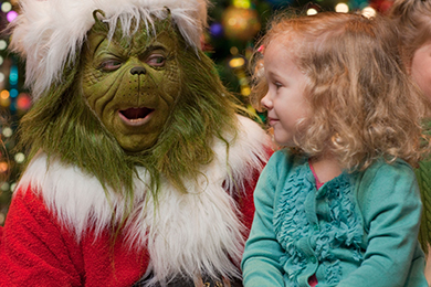 The Grinch sits with a young blond girl at Grinchmas.