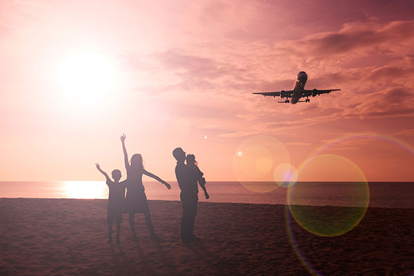 Family watching a plane fly overhead from the beach.