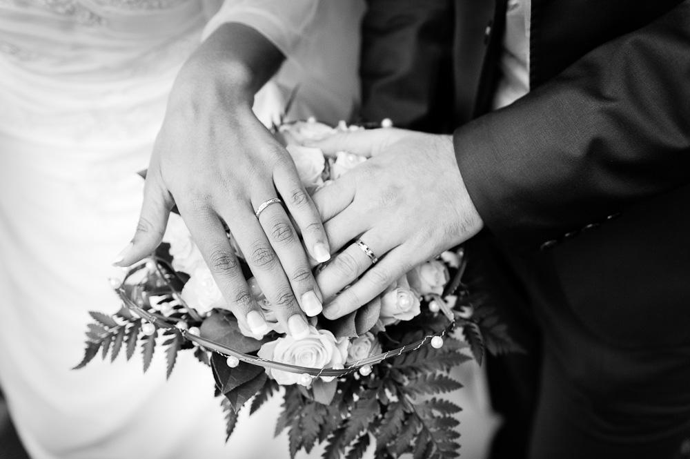 Mains de mariés, focus sur les alliances et le bouquet.