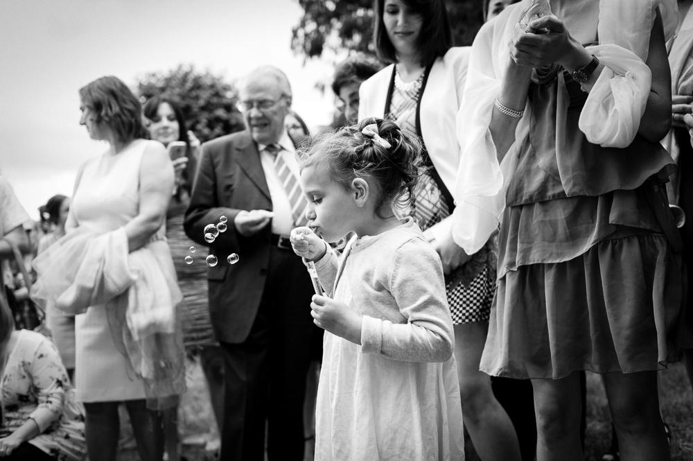 Photo de mariage en noir et blanc d'une petite fille faisant des bulles avant la sortie des mariés devant l'église.