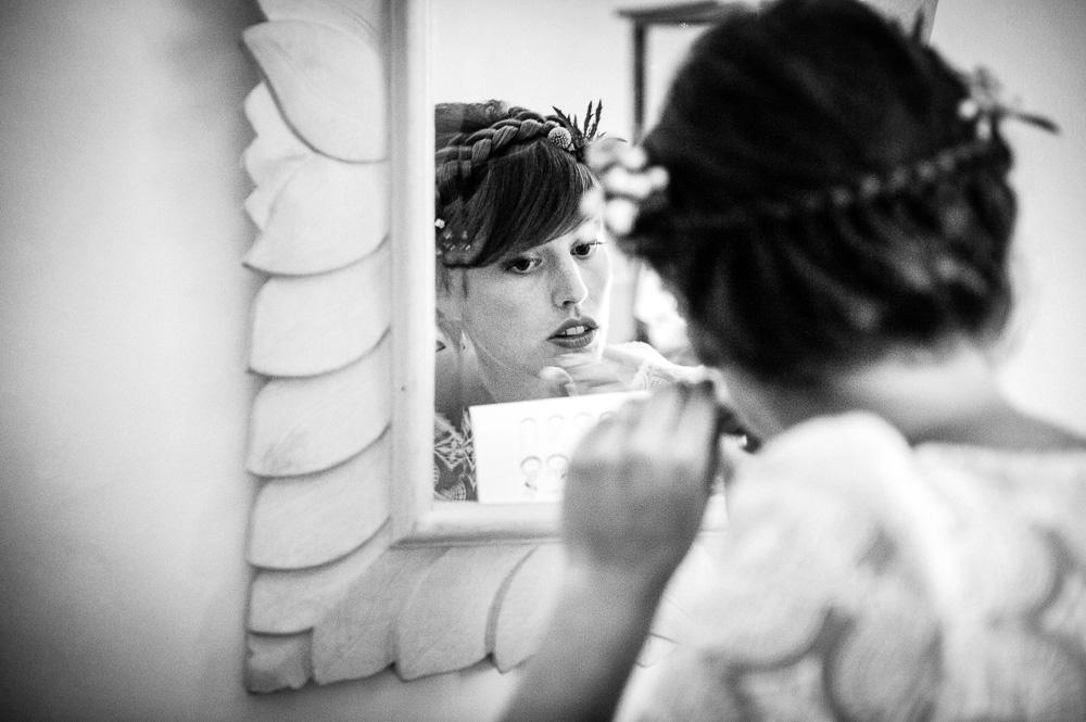 Photo noir et blanc d'une mariée en plein préparatifs de maquillage devant un miroir.