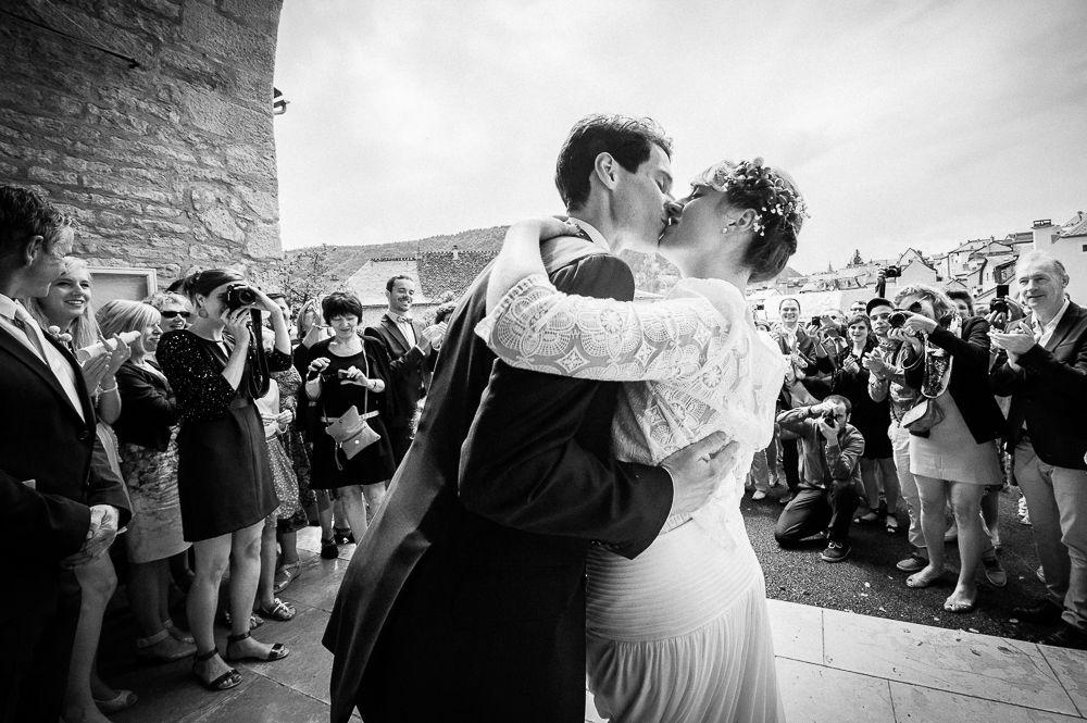 Baiser des mariés à la sortie de l'église lors d'un mariage en lozère.