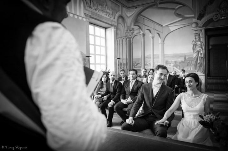 Mariage civil à la mairie de clermont-ferrand dans le puy-de-dome (63). Les mariés regardent le maire qui lit l'acte de mariage et sourit de bonheur.