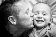 Photographie noir et blanc d'un papa embrassant son fils sur la joue lors d'une séance à domicile. © Fanny Reynaud photographe à domicile.