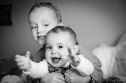 Deux jeunes enfants jouent sous le regard du photographe. Image prise durant un shooting à domicile à volvic, près de clermont-ferrand, par un photographe professionnel.