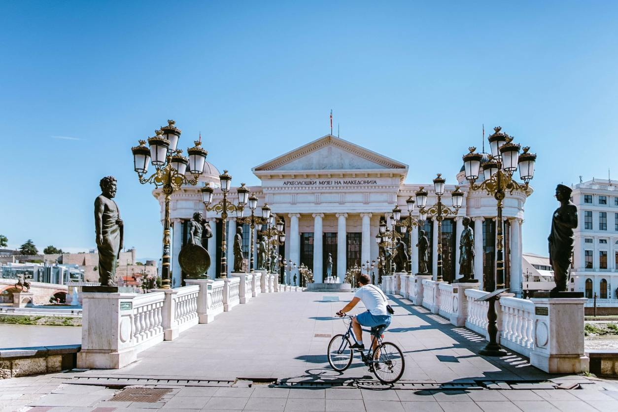 man-cycling-across-a-bridge-in-a-european-city-in-summer-towards-an-old-historic-building-tourist-attraction-interrail-budget-interrailing-on-a-budget