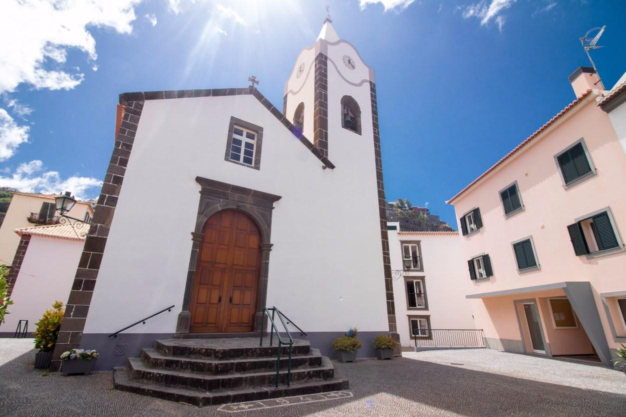 Маленькая белая европейская церковь в деревне Понта-ду-Сол на фоне голубого неба Мадейра