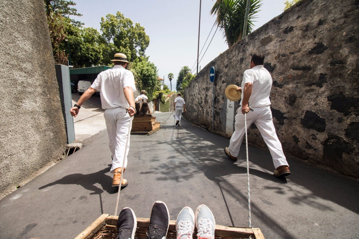 two-men-in-white-clothing-dragging-a-wicker-toboggan-sled-ride-from-monte-to-funchal