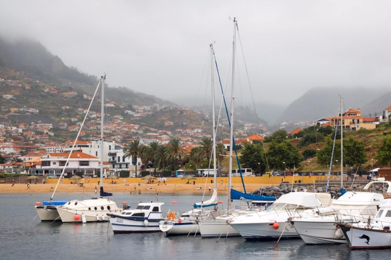 лодки-на-воде-у-гавани-за-машинкой-деревней-в-горах-в-туманный-день Мадейра