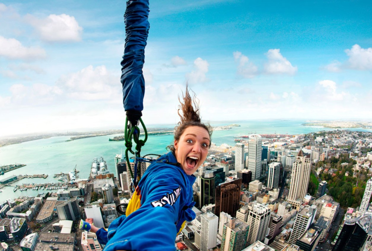 woman-screaming-and-jumping-off-skyscraper-whilst-connected-to-bungee-cord-in-a-city-with-buildings-and-a-harbour-in-the-background-sky-tower-auckland
