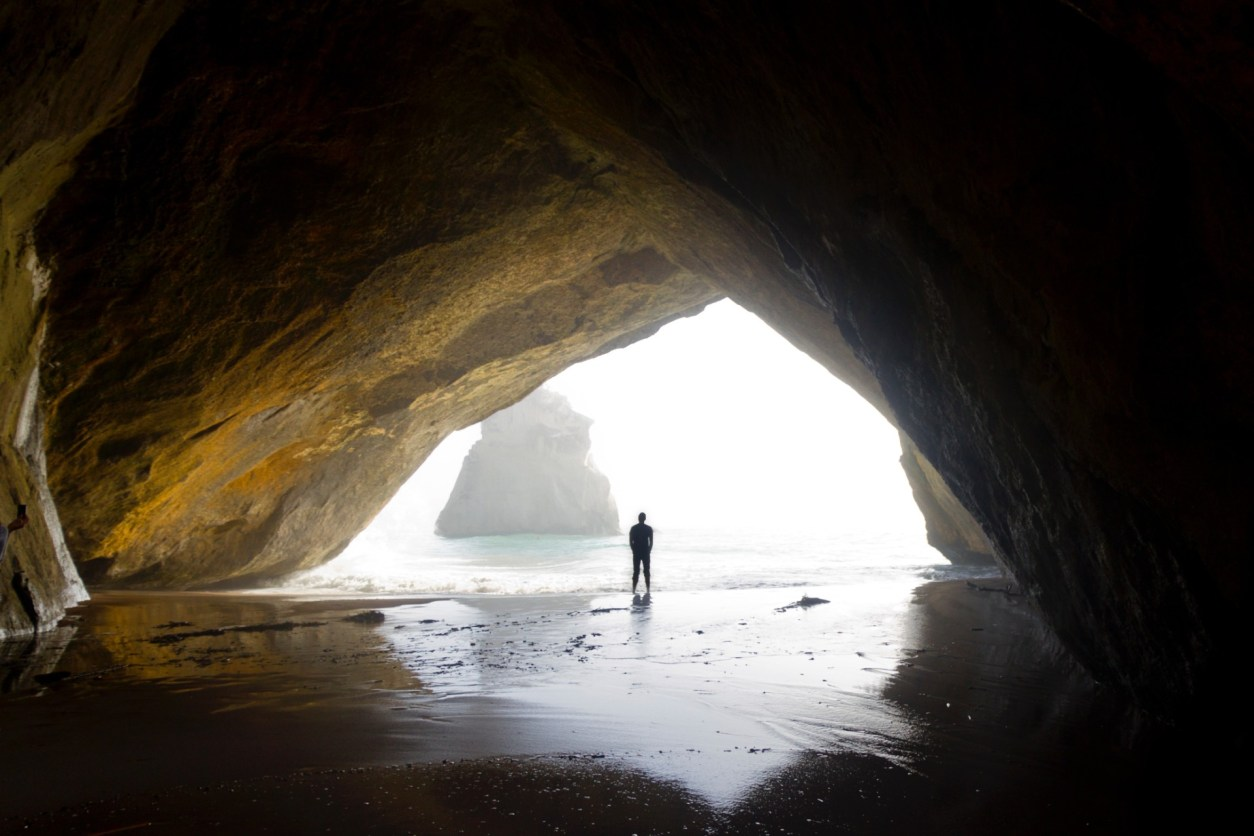 silhouette-of-a-man-standing-within-a-sheltered-cove-on-a-beach-cathedral-cove