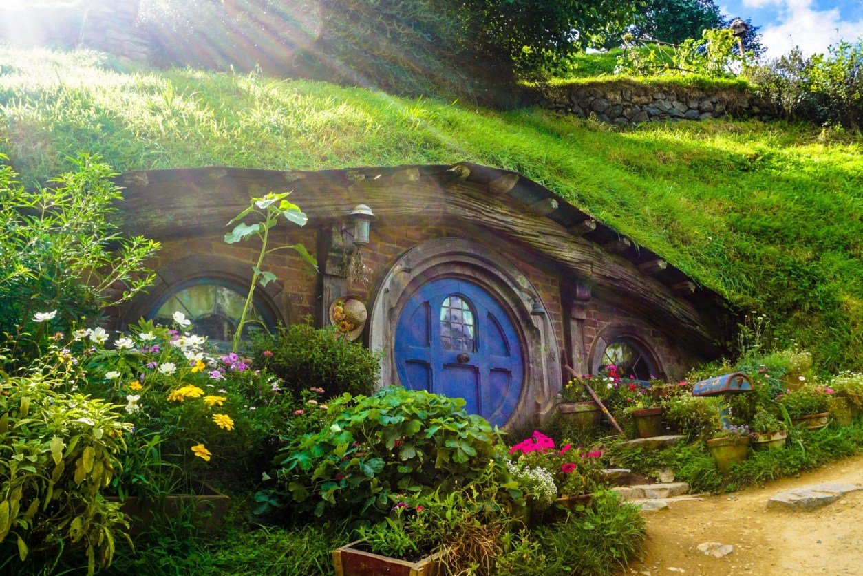 small-house-under-a-green-hill-with-a-round-blue-door-hobbiton-lord-of-the-rings-new-zealand-bucket-list