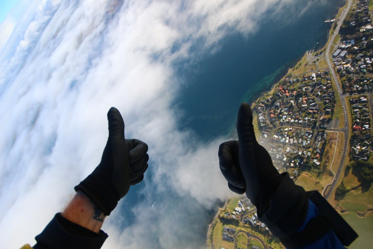 Thumbs up with gloves town below green fields blue lake clouds Skydive Taupo The Best Skydiving in New Zealand