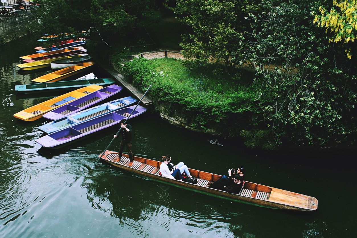 Punting along the river in Oxford. People in boat. Boats in river. Greenery and trees. How to Spend One Day in Oxford: Best Things to Do. Oxford England. Oxford UK. Oxford University. 24 hours in Oxford. Oxford in One Day. Things to do in Oxford. Places to see in Oxford. Places to Visit in Oxford. What to see in Oxford. Things to see in Oxford. What to do in Oxford. Oxford attractions. Oxford top attractions. Oxford travel blog. Oxford travel guide. Oxford Castle. Turl Street. Oxford bookshops. Bridge of Sighs. Bodleian Library. Radcliffe Camera. University Church of St Mary. Oxford punting. Click through to read more...