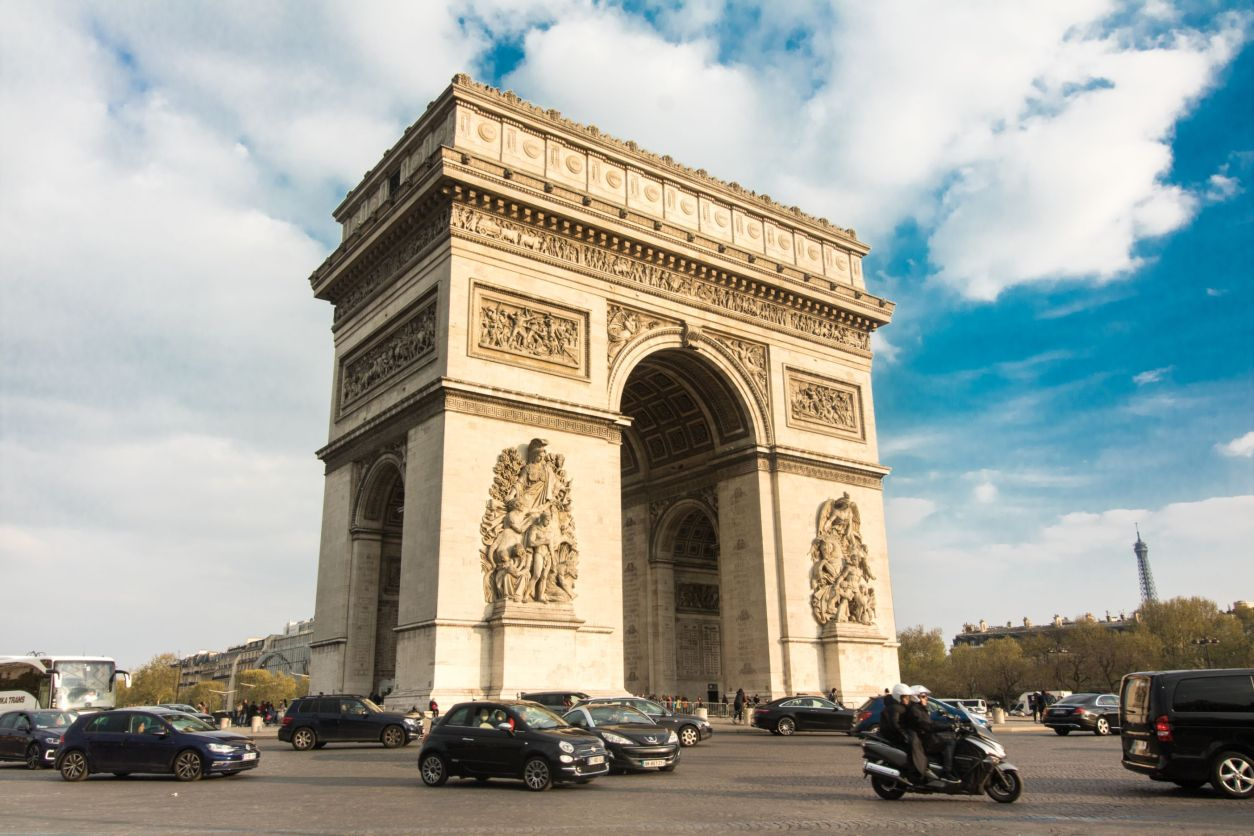 Arc de Triomphe. Cars driving in front of a famous arc and landmark in Paris on a sunny evening at golden hour.