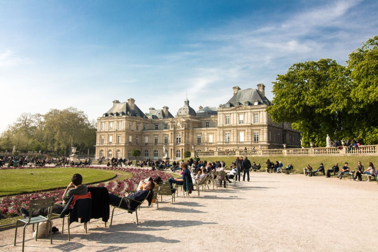 Palais du Luxembourg and Jardin du Luxembourg Paris. People relaxing and sunbathing in a park, sat on chairs, in front of a grand old historic building. Blue skies and trees.