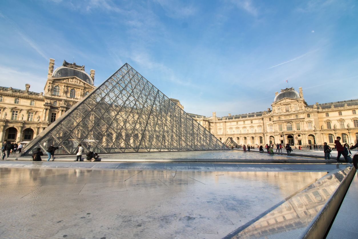 Louvre Museum and Art Gallery Paris. Glass pyramid in square with historic buildings and blue skies in background. Fountains in foreground.