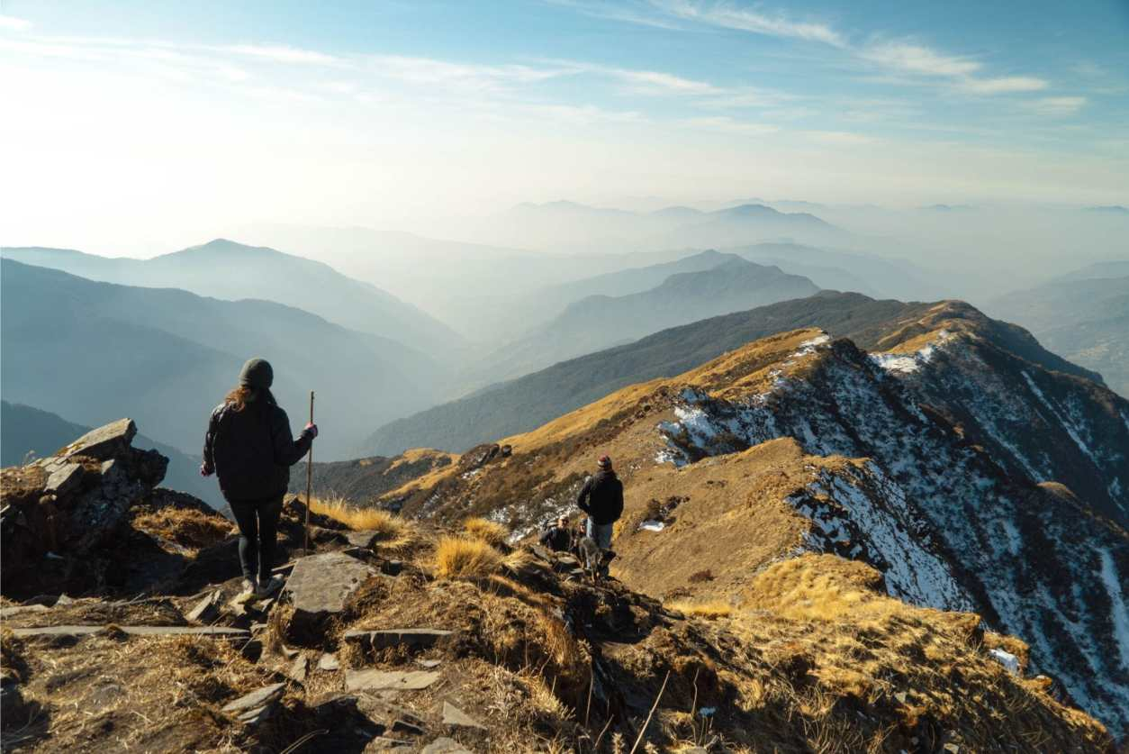 people-stood-on-snowcapped-mountains-hiking-walking-sustainable-travel-tips