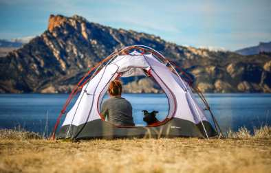 woman-in-tent-with-dog-camping-on-the-grass-near-a-lake-and-mountains-sustainable-travel-tips