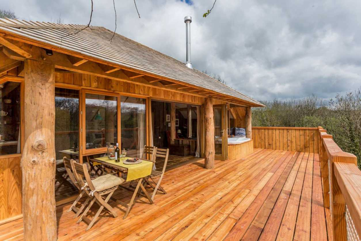 large-balcony-of-treehouse-with-a-dining-table-and-chairs-and-hot-tub-wolf-wood-treehouses-okehampton-devon-treehouse-holidays-uk-with-hot-tub
