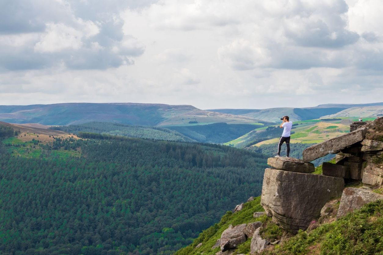 man-standing-on-a-dangerous-rock-edge-on-a-hill-taking-a-photo-across-the-forests-to-his-left-at-bamford-edge-in-the-peak-district