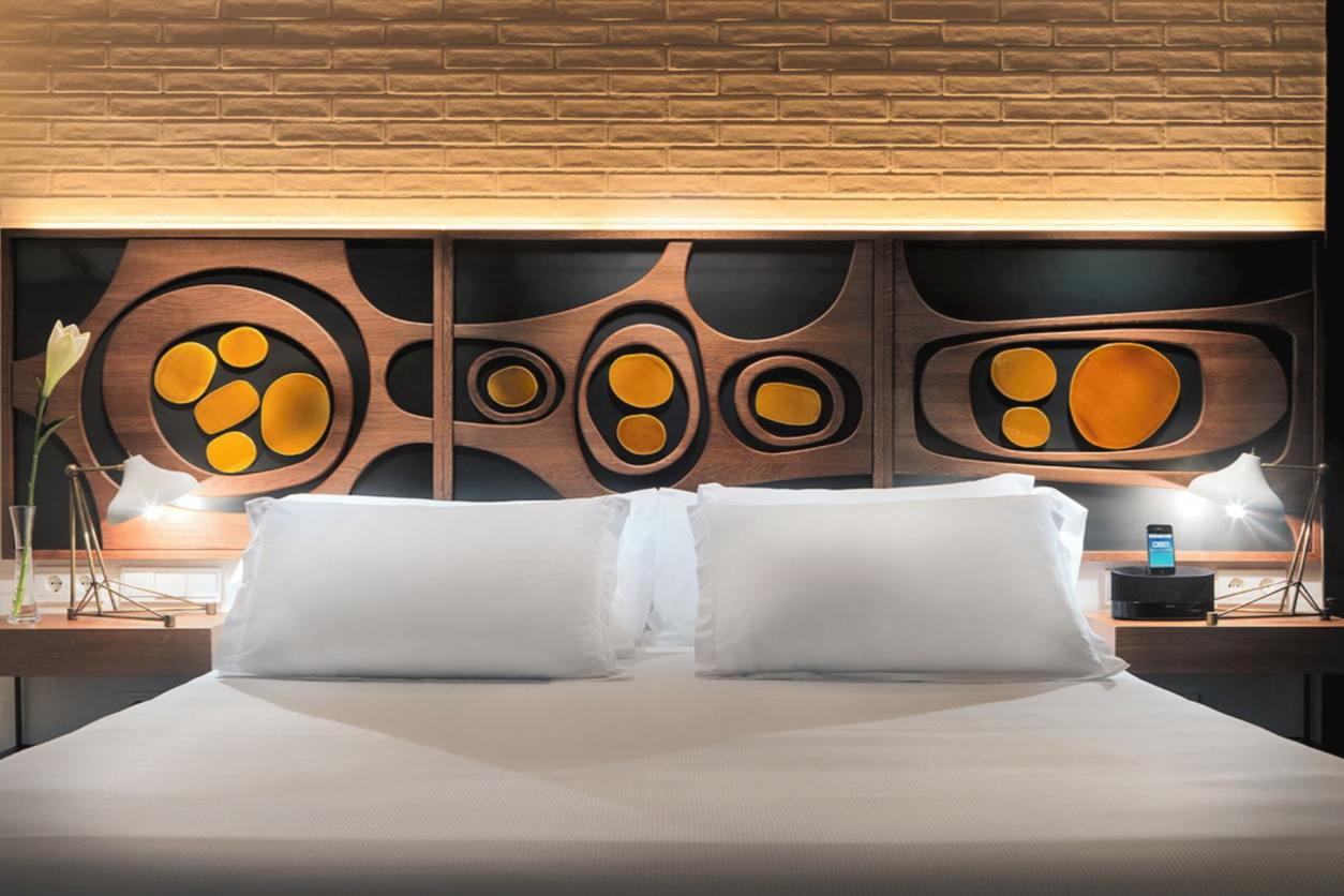 art-deco-retro-decor-in-hotel-room-bed-with-white-pillows-and-cover-at-h10-metropolitan-hotel-barcelona