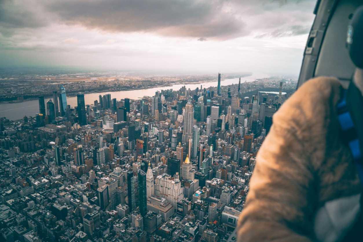 woman-sat-in-open-door-helicopter-flying-across-new-york-city-flynyon