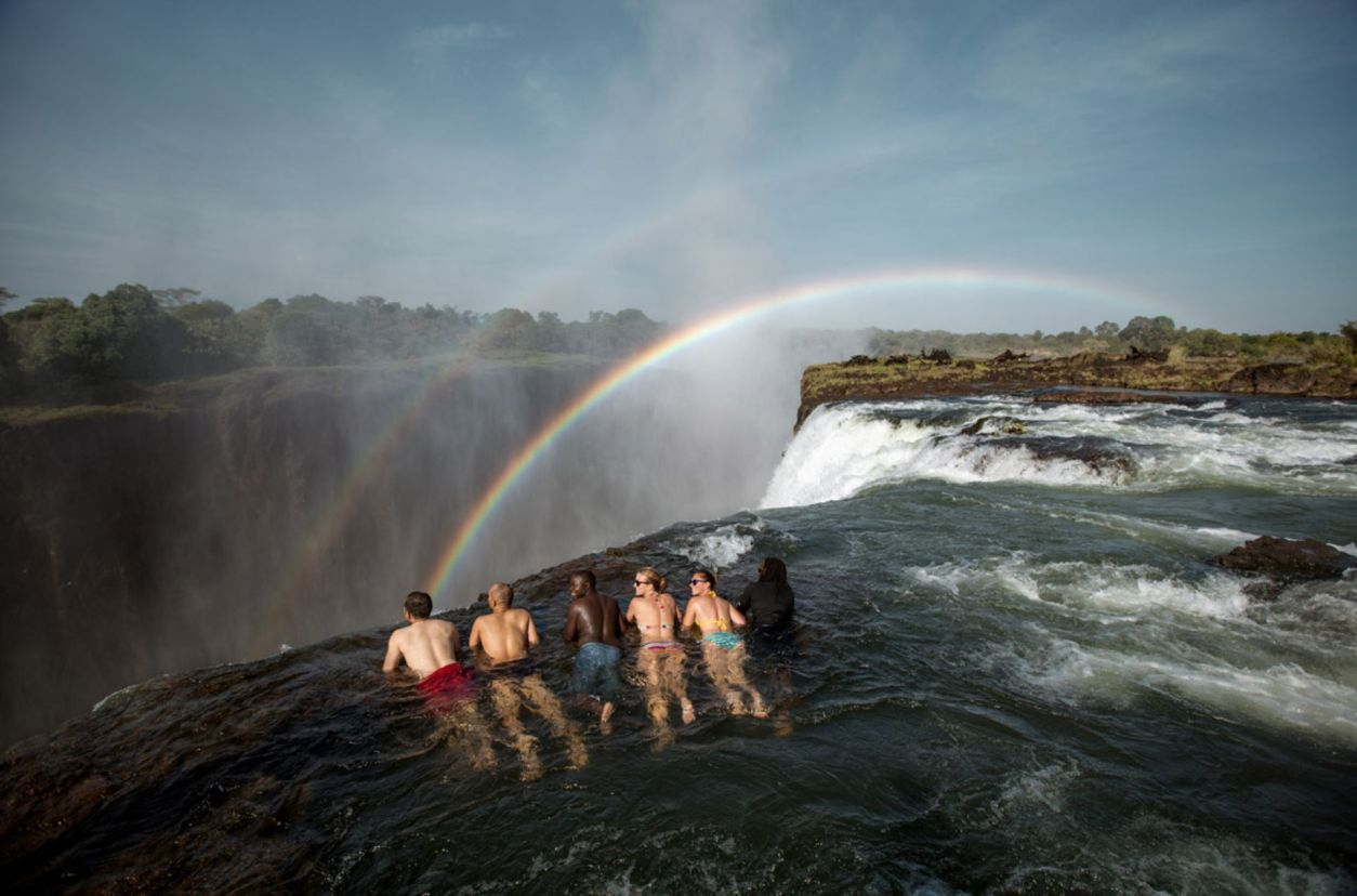 group-of-friends-lying-down-in-the-water-at-the-edge-of-victoria-falls-zambia-adrenaline-junkie-bucket-list