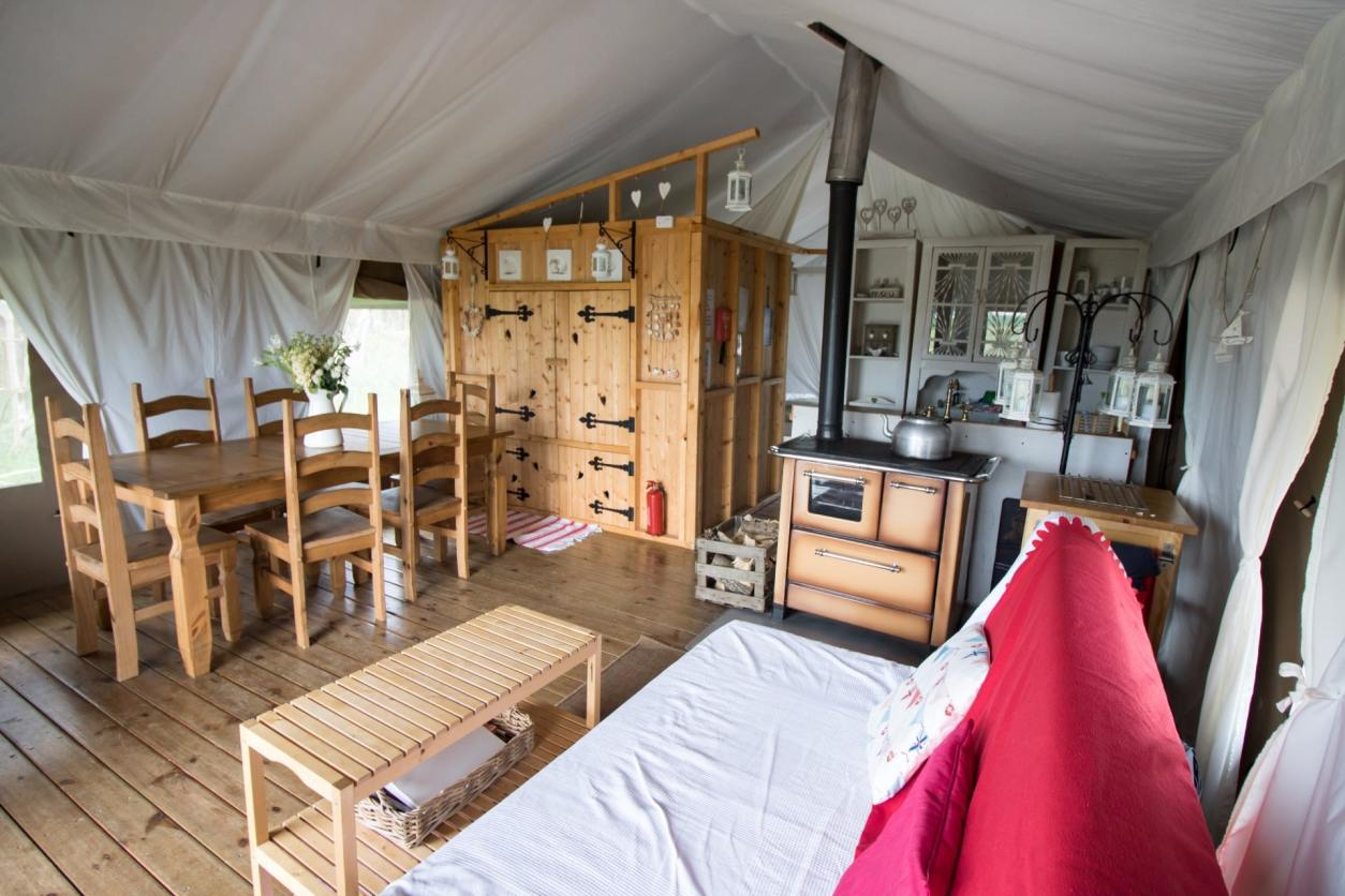 inside-a-safari-tent-glamping-site-with-kitchen-bed-table-and-sofa-harvest-moon-holidays-scotland-unusual-romantic-weekend-breaks-uk