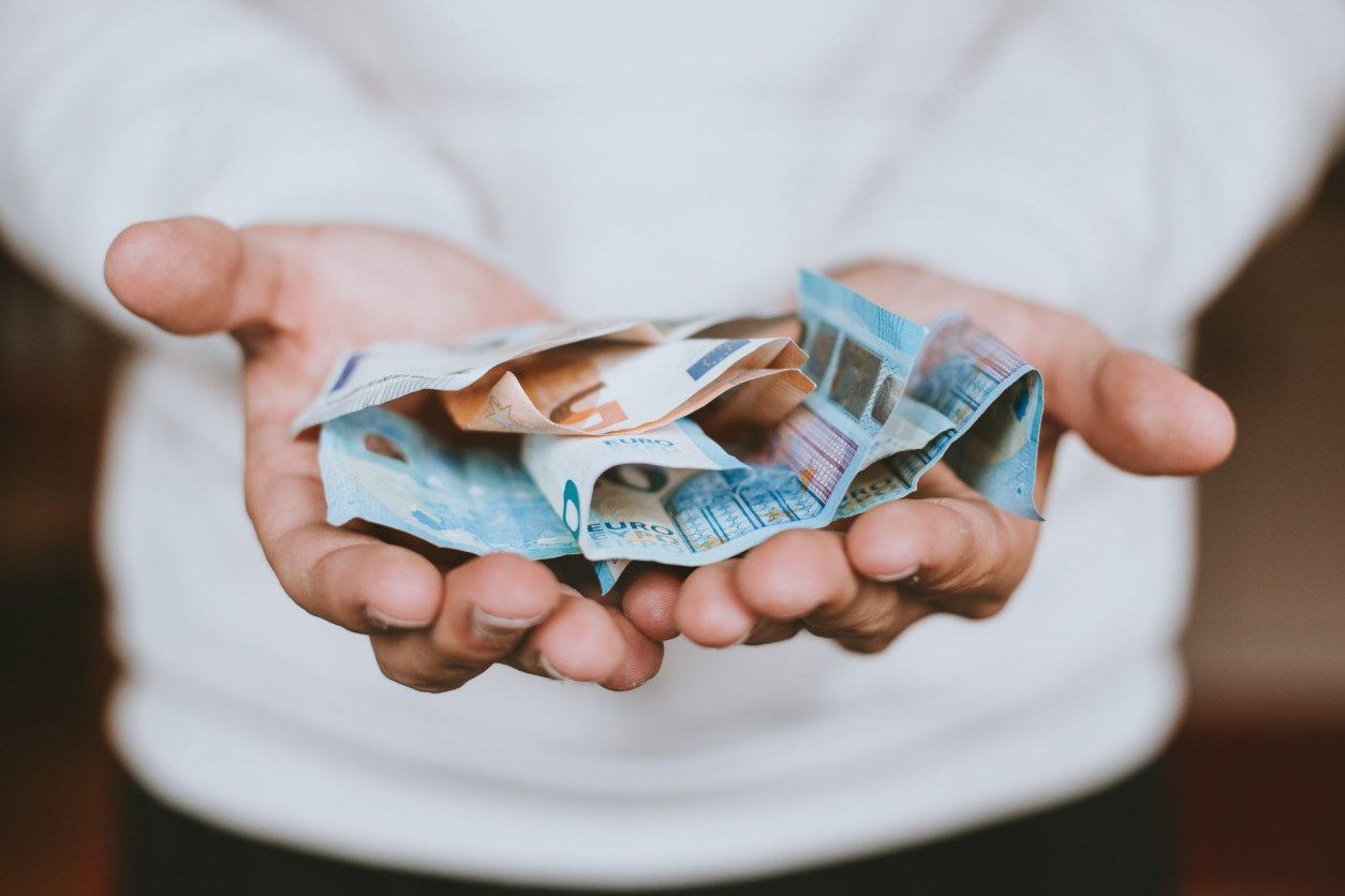 man-in-white-jumper-holding-his-hands-out-holding-euro-notes-money-in-his-palms