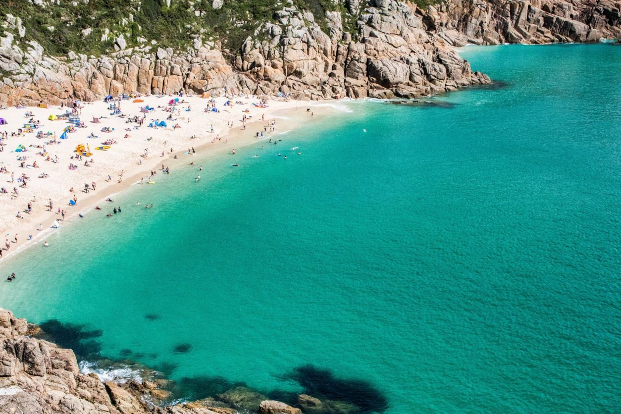 aerial-image-of-porthcurno-beach-from-above-by-minack-theatre-people-sunbathing-on-beach-beside-turquoise-waters-cornwall-hidden-gems