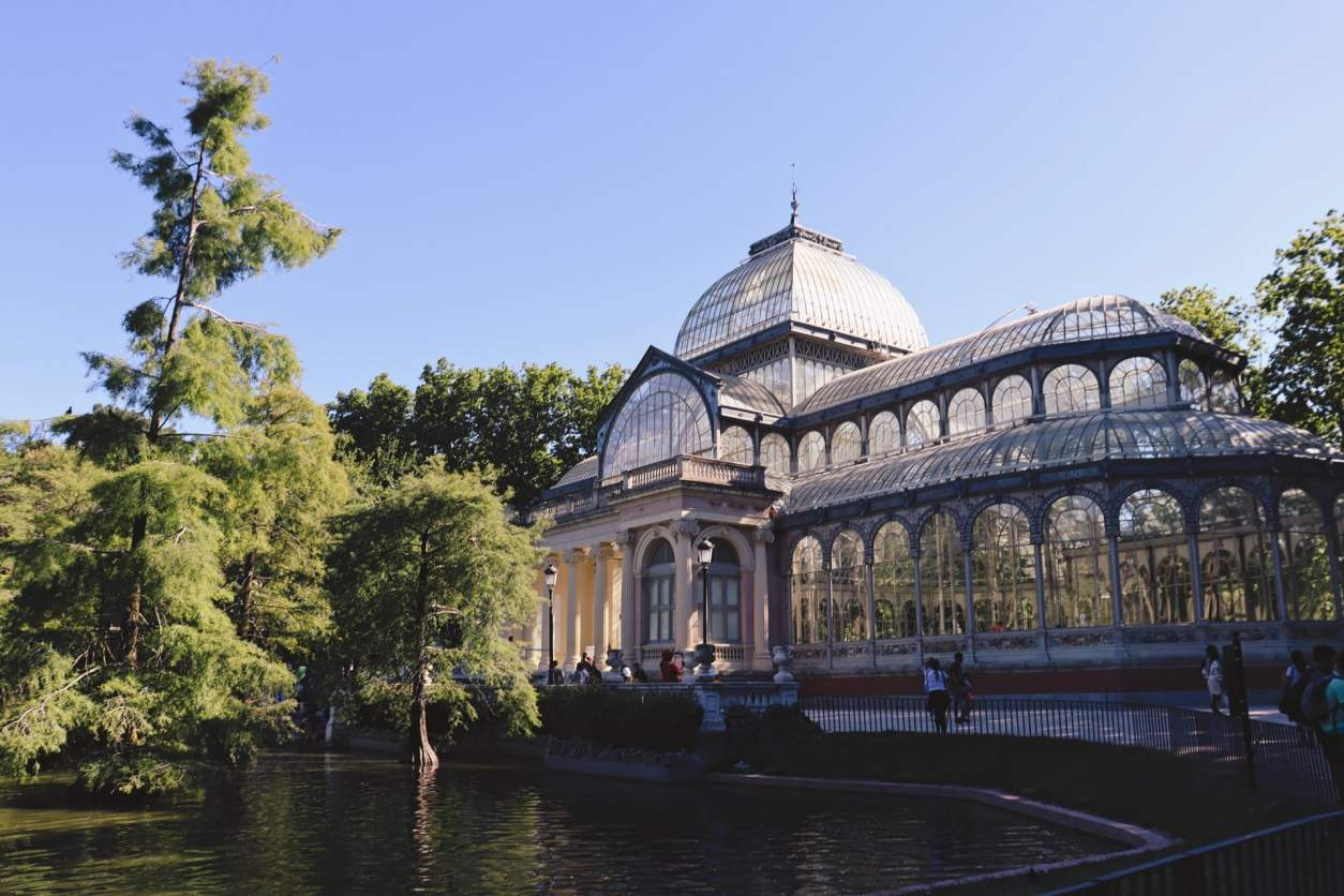 glasshouse-in-park-on-a-sunny-day-by-a-pond-and-trees-in-el-retiro-park-madrid