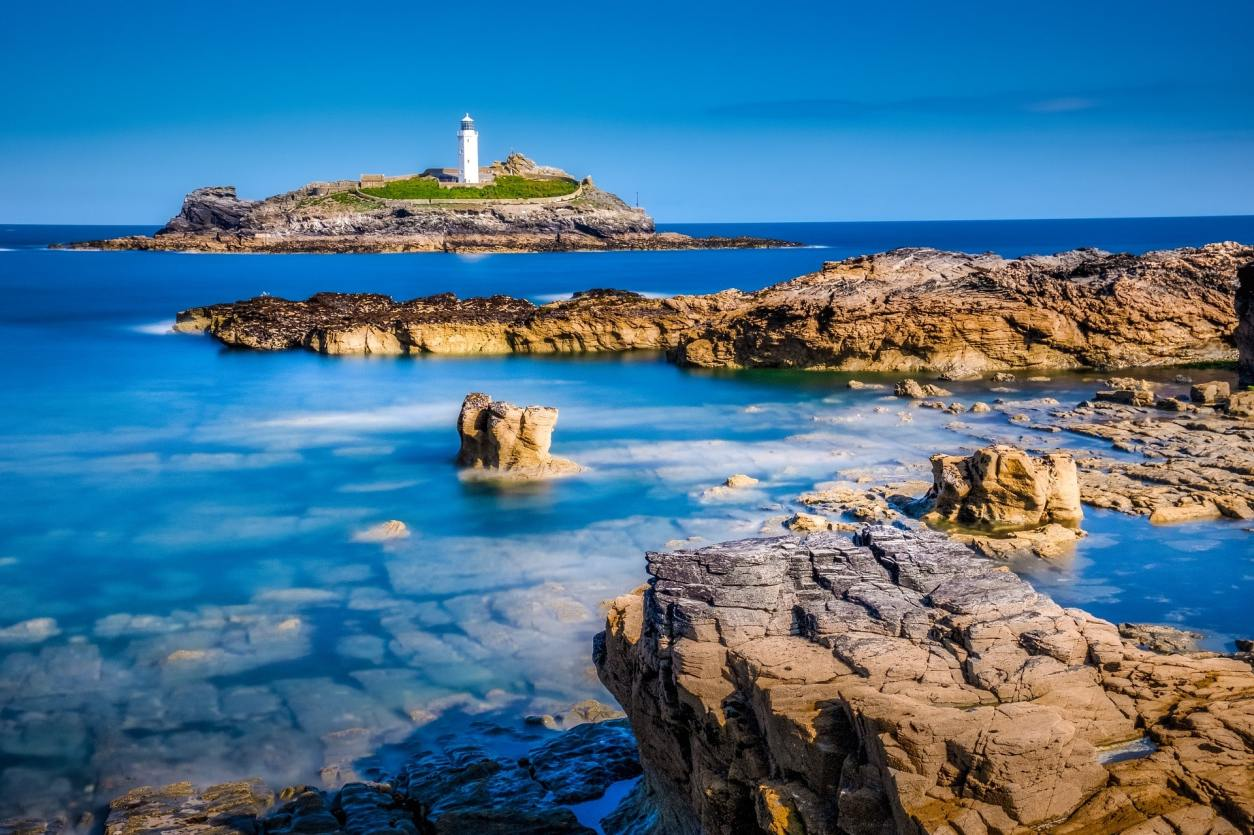 lighthouse-on-rocks-at-sea-with-blue-rockpools-in-foreground-godrevy-lighthouse-cornwall-hidden-gems