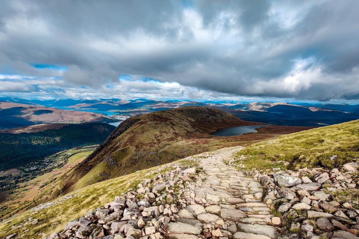 path-leading-up-mountain-with-lake-and-other-mountains-in-background-ben-nevis-scenic-drives-in-scotland